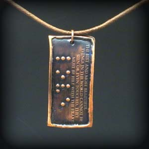 dark copper pendant with the word love brailled on it and in raised letters, the following quote:  The best and most beautiful things in the world cannot be seen or even touched, they must be felt with the heart. - Helen Keller