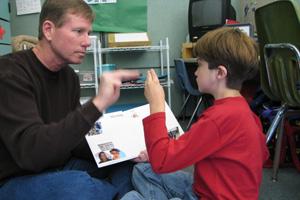 Dylan y un adulto hablan con lenguaje de señas