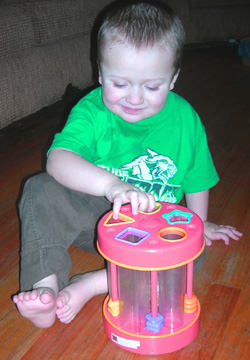 Eddie playing with a shape sorting toy