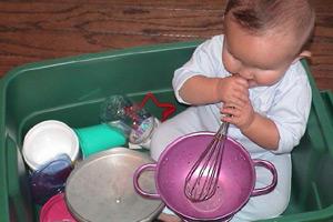 bebé en una tina de plástico con utensilios de cocina