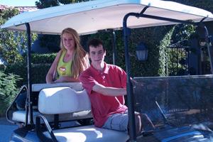 dos hermanos en un vehículo de golf