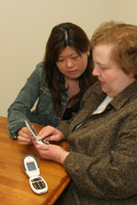 Two women inspecting a cell phone.