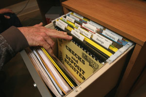 a file drawer opened to reveal files and a large-print check register