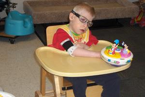 Un niño en una silla de ruedas adaptada trata de alcanzar un juguete