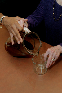 a   woman pouring a drink and placing her finger on the inner lip of a glass to know when it is full