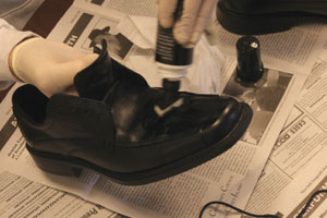 close up of man's hands applying polish to a black shoe using a bottle with a built-in foam applicator