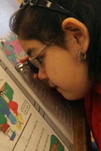 girl using a magnifier to read her schoolwork