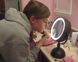 la chica adolescente utiliza un espejo