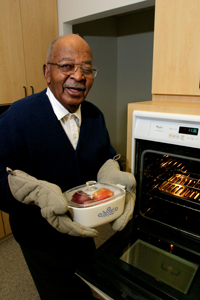 Man wearing   oven mitts placing baking dish in oven