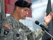 A photo of Jeff Mittman in uniform speaking into microphone