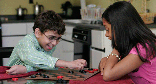 Low vision boy and girl playing checkers