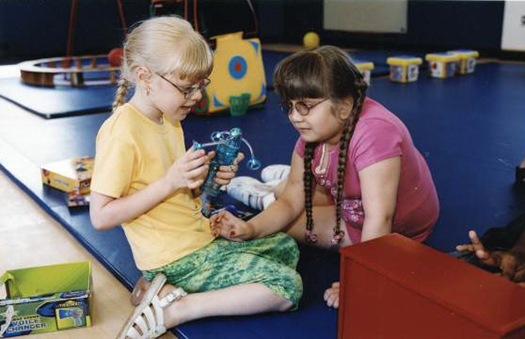 two girls playing with a voice-changing toy