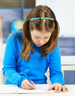 An elementary school age girl in a blue shirt writing at her desk