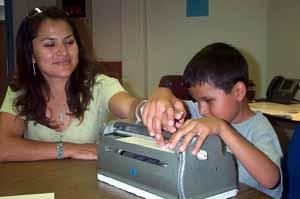 Aaron le toma la mano de su madre y la pone sobre la escritura en relieve
