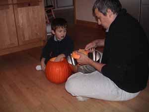 papá y niño preescolar tallan una calabaza