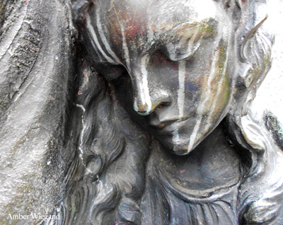 closeup on the weather-streaked statue of an angel