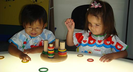 Dos niños de edad preescolar con impedimentos visuales juegan con anillos apilables de vivos colores sobre una mesa brillante.