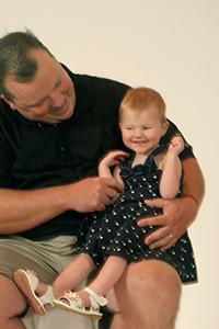 Padre sonriendo a su joven hija con discapacidad visual, que esta sentada en sus piernas, sonriendo.